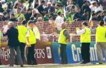 Stewards hold up netting to prevent Pakistani fans entering the field after Steve Waugh leads his team off the field