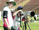 Zimbabwe cricketer Dirk Viljoen looks through a photographer's camera as his teammate Travis Friend (L) holds his cap during a practice session at Jodhpur cricket ground 07 December 2000, in Jodhpur. Zimbabwe will play its third one-day cricket match against India 08 December. India leads the series 2-0.